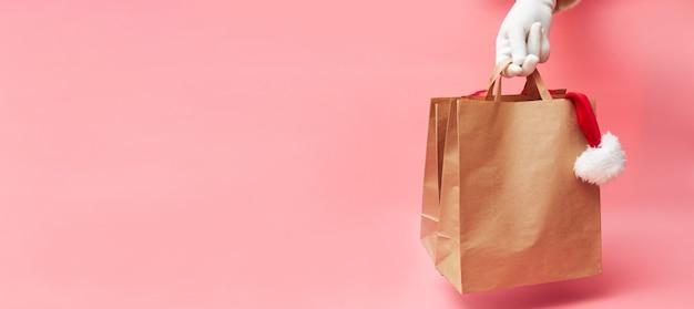 Concetto di natale, due sacchetti di carta in mano, sconti su vestiti e accessori, su sfondo rosa