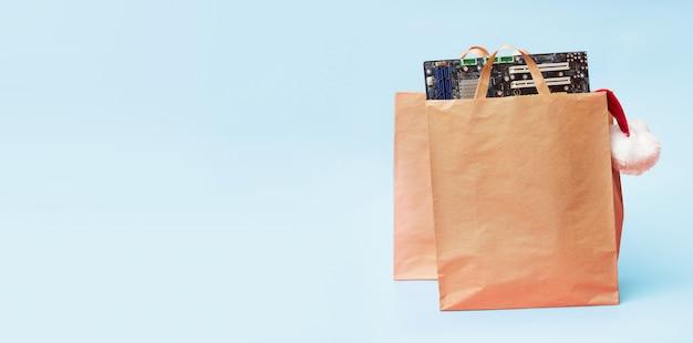 Concetto di natale, due sacchetti di carta con accessori per computer di bordo di circuiti portuali, su sfondo blu
