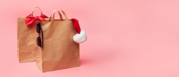 Concetto di natale, due sacchetti di carta artigianale, sconti sugli accessori, su uno sfondo rosa, banner