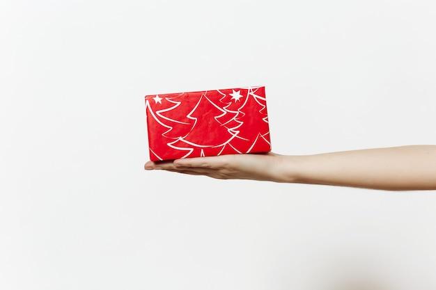 Concetto di natale con la mano femminile e tenendo la scatola rossa presente. regalo isolato su sfondo bianco da vicino.