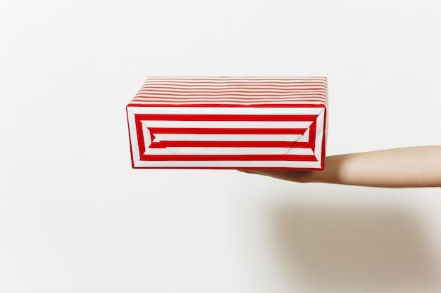 Concetto di natale con la mano femminile e tenendo la scatola presente a strisce rosse. regalo isolato su sfondo bianco da vicino.