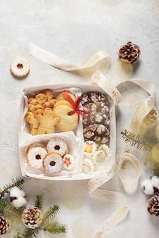 Concetto di natale con biscotti fatti a mano e confezione regalo, immagine di messa a fuoco selettiva e vista dall'alto in basso