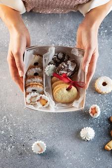 Concetto di natale. donna che mantiene biscotti fatti a mano e confezione regalo, immagine di messa a fuoco selettiva