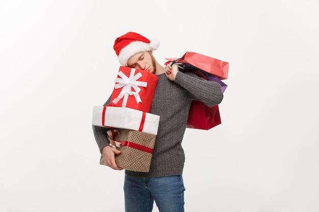 Concetto di natale - giovane uomo bello con la barba che tiene regali pesanti con l'espressione facciale esausta sul muro bianco.