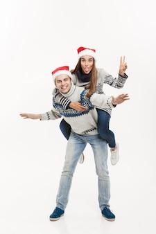 Concetto di natale - giovani coppie felici in maglioni che godono del giro sulle spalle isolato sul muro grigio bianco.