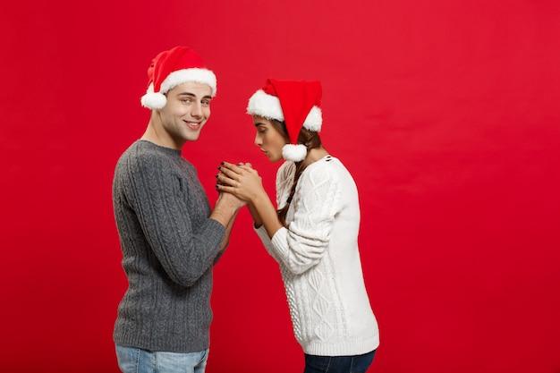 Concetto di natale - giovani coppie alla moda che si tengono per mano in inverno.