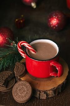 Contenuto natalizio, tazza rossa con cacao, lecca-lecca, supporto in legno, biscotti al cioccolato, ramo di abete, albero di natale, palline rosse, sfondo scuro