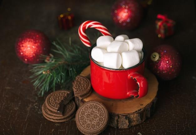 Contenuto natalizio, tazza rossa con cacao, marshmallow, lecca-lecca, supporto in legno, biscotti al cioccolato, ramo di abete rosso, palline rosse, sfondo scuro