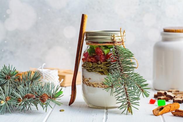 Barattolo per biscotti natalizi. ingredienti secchi per cucinare i biscotti di natale in un barattolo, sfondo bianco.