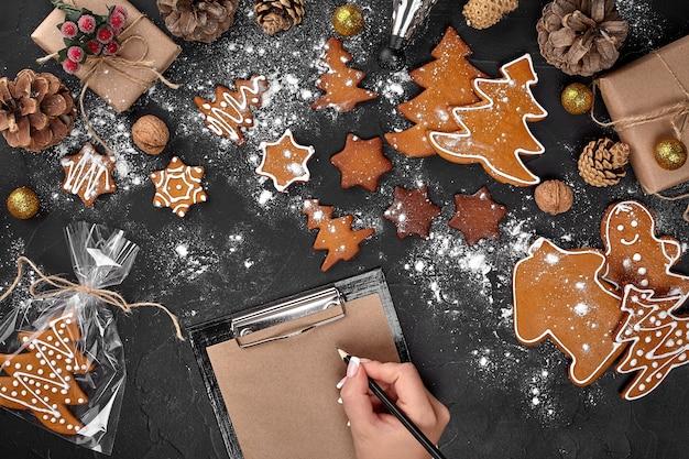 Albero di biscotti di natale realizzato con formine per biscotti a stella, pan di zenzero, pasticceria di capodanno, decorata con fiocco in corda e forma per ritagliare i biscotti sul tavolo nero. cibo delizioso di pasticceria dolce festivo