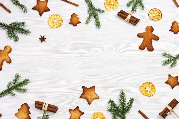 Biscotti di natale assortiti vista dall'alto, rami di abete verde, bastoncini di cannella, arance secche su bianco