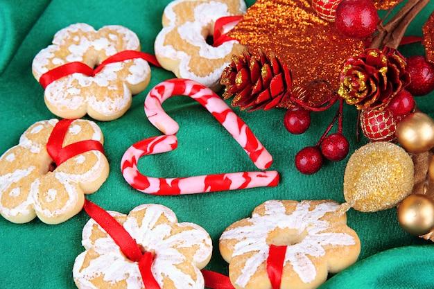 Biscotti e decorazioni natalizie su sfondo di tessuto colorato
