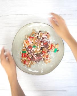 Biscotti di natale, biscotti dell'uomo di pan di zenzero con zucchero a velo su piatto naturale, trama di fondo in legno bianco, vista dall'alto fatta in casa