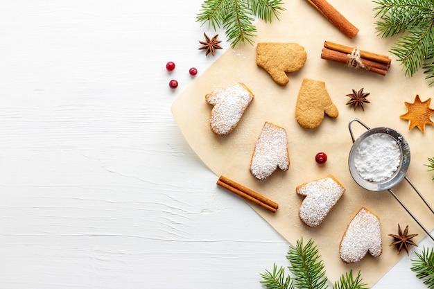 Biscotti-muffole di natale su carta da forno con bastoncini di cannella sulla tavola di legno bianca