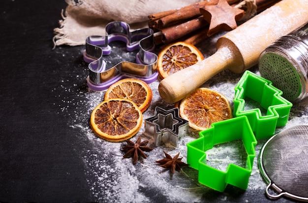 Cucina natalizia: ingredienti da forno, stelle di anice e bastoncini di cannella su sfondo scuro