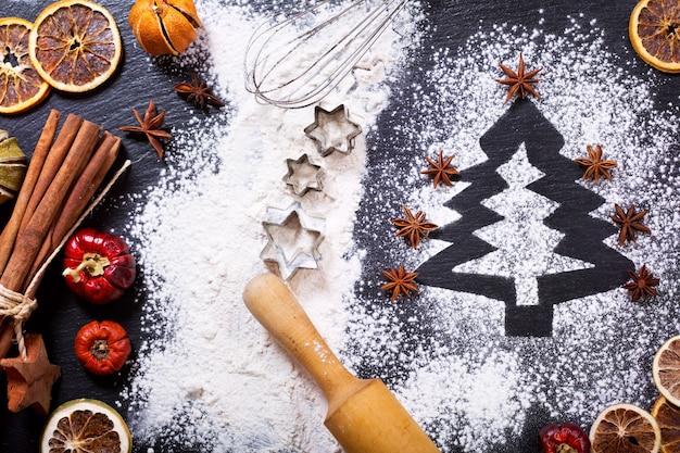 Cucina natalizia: abete fatto con farina su un tavolo scuro, ingredienti per la cottura e frutta secca su sfondo scuro, vista dall'alto