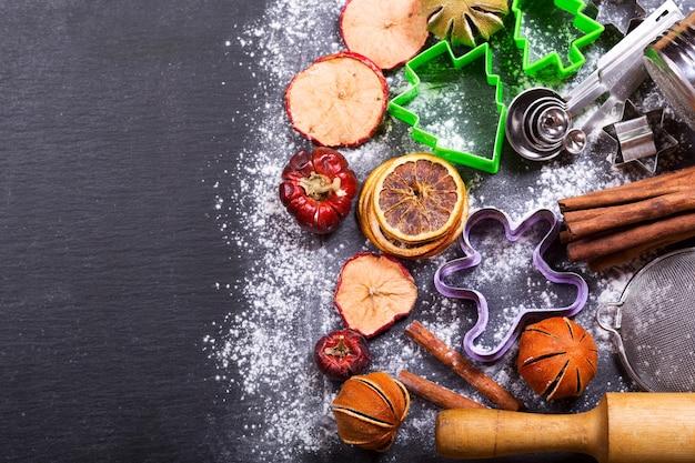 Natale cucina utensili da cucina e frutta secca su sfondo scuro vista dall'alto