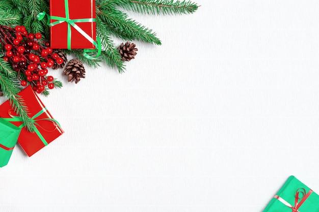 Angolo di natale con rami di abete verde, decorazioni e regali di natale su sfondo bianco.