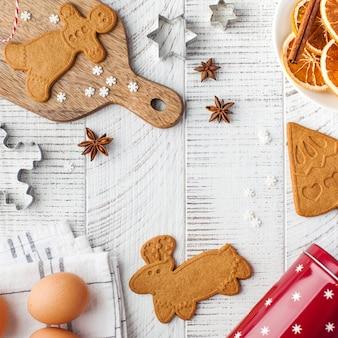 Superficie accogliente di natale con biscotti allo zenzero e stampi per biscotti su una superficie di legno