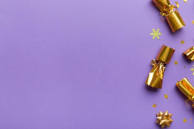 Cracker di natale con coriandoli lucidi su sfondo colorato, vista dall'alto, spazio copia