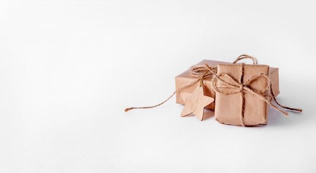 Contenitori di regalo del mestiere di natale su uno spazio bianco. composizione minima creativa. banner.