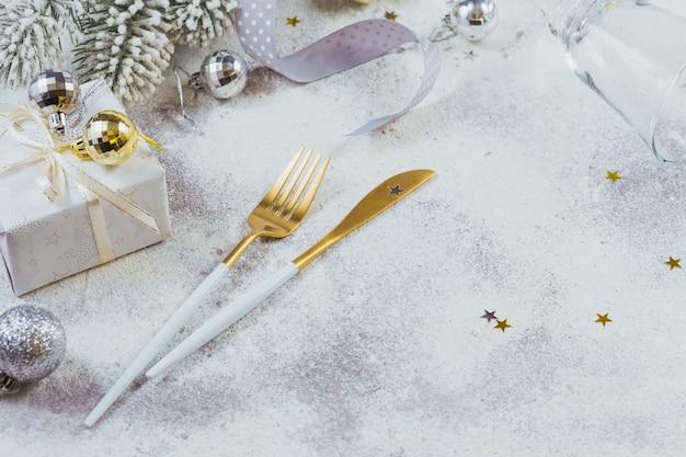 Composizione creativa natalizia con posate, regalo di natale, rami di abete, decorazione. priorità bassa di vacanze invernali. confine, copia spazio.