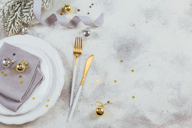 Composizione creativa natalizia con posate, regalo di natale, rami di abete, decorazione. priorità bassa di vacanze invernali. bordo, piatto, vista dall'alto, copia spazio.