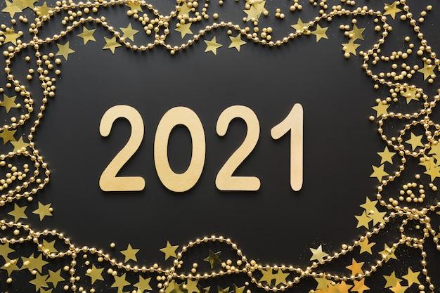 Bordo lucido creativo di natale di data dorata e perline su uno spazio nero con data 2021 anno nuovo
