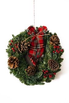 Corona di natale e decorazione ghirlanda invernale con agrifoglio, vischio, abete, abete rosso blu, pigne su sfondo bianco.