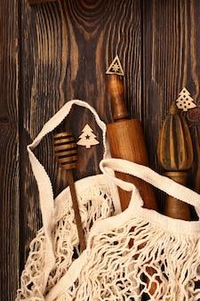 Disposizione culinaria di natale su un fondo di legno. articoli da forno in legno in un sacchetto ecologico. shopping per la tavola delle feste. vista dall'alto, stile piatto.