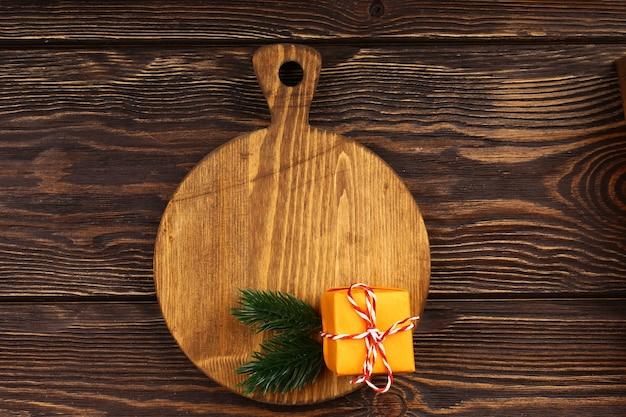 Disposizione culinaria di natale su un fondo di legno. tagliere in legno con oggetti natalizi per il menu della tavola delle feste. vista dall'alto, stile piatto.