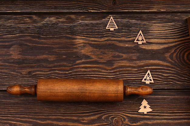 Disposizione culinaria di natale su un fondo di legno. mattarello in legno con elementi dell'albero di natale per il menu della tavola festiva. vista dall'alto, stile piatto.