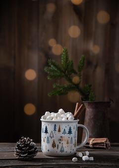 Tazza di natale di cacao e marshmallow con cannella su un vecchio tavolo di legno marrone con bokeh, coni e abete. stato d'animo del nuovo anno. vista frontale e copia spazio