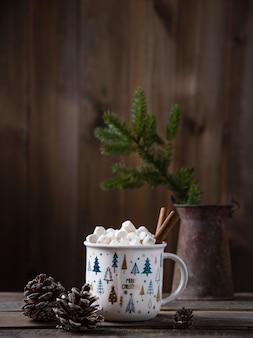 Tazza di natale di cacao e marshmallow con cannella su un vecchio tavolo di legno marrone con coni e abete. stato d'animo del nuovo anno. vista frontale e copia spazio