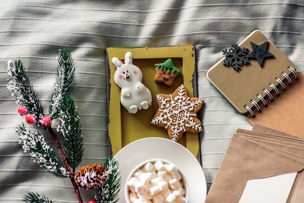 Coppa di natale di cacao con marshmallow, deliziosi biscotti di capodanno sul letto w. concetto di inverno. accogliente dolce casa. nessuno al coperto.