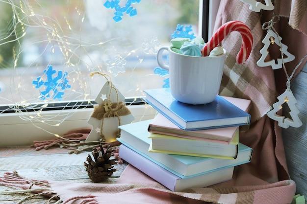 Natale una tazza di caffè decorazione una pila di libri illuminazione sullo sfondo di una finestra