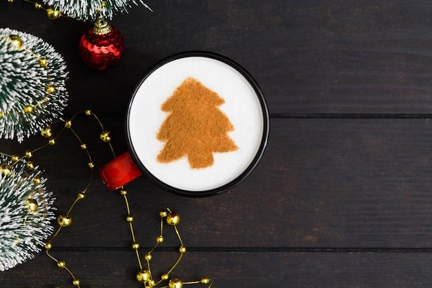 Tazza di caffè di natale con l'albero di abete. bevanda di capodanno sulla tavola di legno