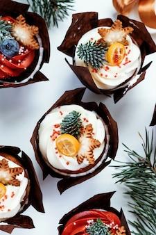 Cupcakes di natale per la decorazione di capodanno. set di pasticcini decorati con bacche, stelle e rami di abete.