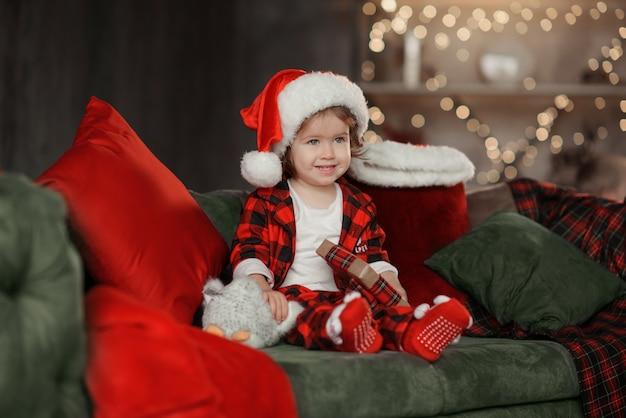Ragazza sveglia del bambino di natale in cappello della santa che tiene un contenitore di regalo.