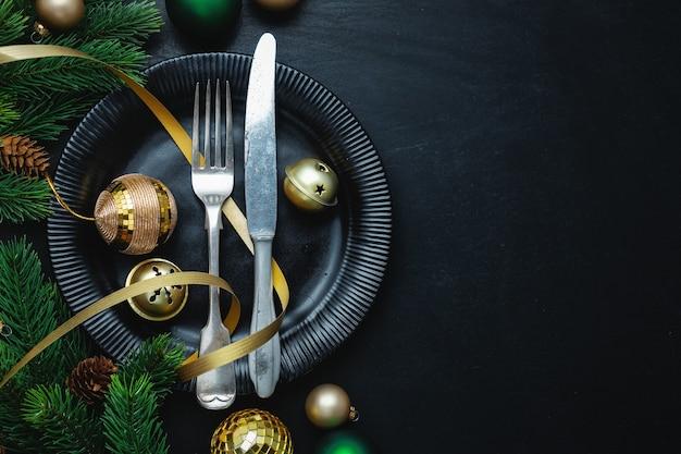 Posate di natale sulla piastra con decorazioni natalizie sul tavolo.