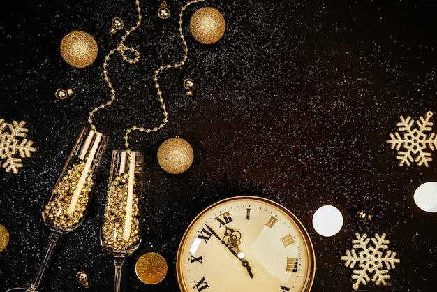 Sfondo scuro di natale. oggetti e decorazioni natalizie dorate, bicchieri, champagne, orologi. concetto di celebrazione di natale. composizione piatta vista dall'alto.