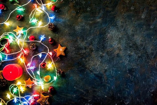 Sfondo scuro di natale con ghirlanda di natale, decorazioni, stelle di panpepato e candele. vista dall'alto copia spazio