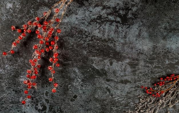 Superficie scura di natale con rami di bacche rosse congelate
