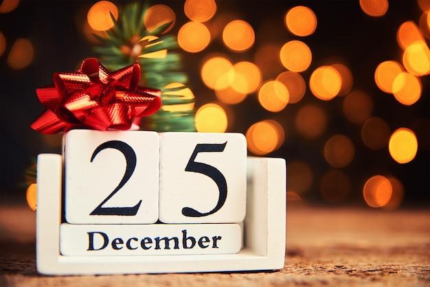 Concetto di giorno di natale. calendario di blocchi di legno con data 25 dicembre su sfondo chiaro bokeh sfocato.