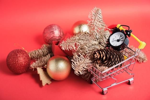 Decorazioni natalizie e piccola sveglia nera in un mini carrello su una superficie rossa