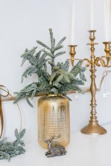 Decorazioni natalizie in un soggiorno classico o rami di abete rosso in vasi d'oro con giocattoli e un candelabro d'oro