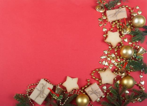 Decorazioni natalizie di rami di abete e abete rosso, palline gialle, scatole regalo e biscotti sul rosso