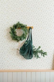 Decorazioni natalizie nel soggiorno in stile scandinavo una ghirlanda di rami di abete sul muro