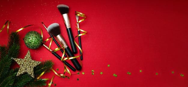 Decorazioni natalizie e cosmetici per il trucco su uno sfondo rosso vista dall'alto banner copy space