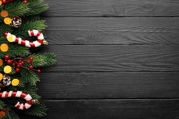 Fondo della decorazione di natale - rami di abete, sorba e bastoncino di zucchero sulla tavola di legno nera. vista dall'alto con copia spazio